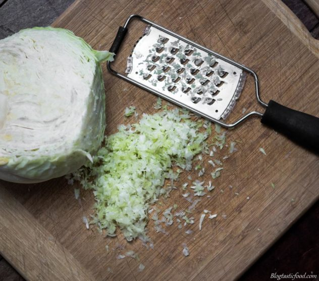 An overhead photo of raw cabbage grated on a chopping board.