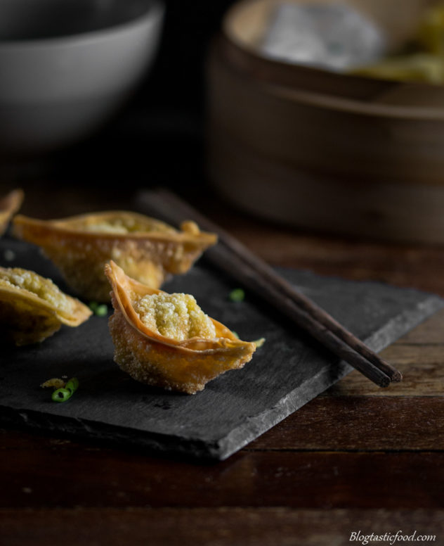 Crispy wontos garnished with chives, showing a steamer and a bowl of wonton soup in the background.