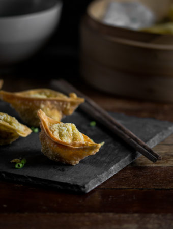 A photo of a few crispy deep fried wontons on a sushi slate with a pair of chopsticks.
