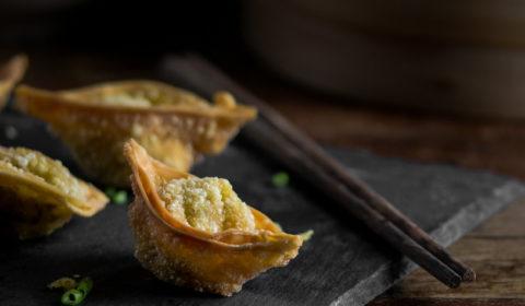 A photo of a few crispy deep fried wontons on a sushi slate with a pair of chopsticks.