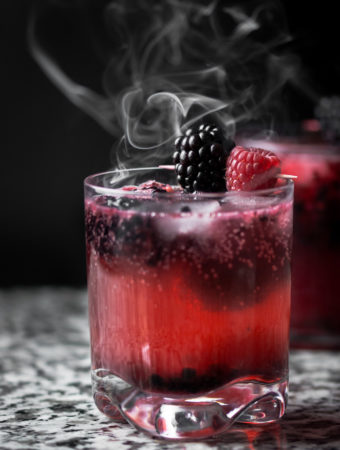2 Black Widow themed cocktails on a granit surface with smoke rising above them.