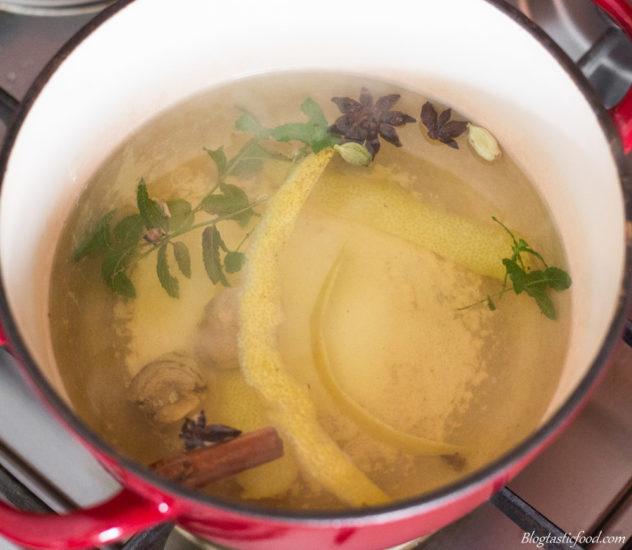 A mixture of herbs and aromatics infusing in a pot of hot water.