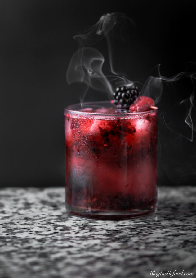 A Black Widow cocktail with smoke in the background.