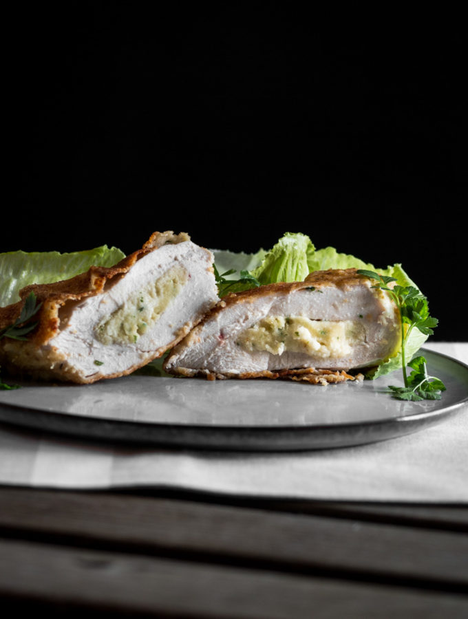 A photo of butter couscous stuffed chicken breasts served on a fancy plate