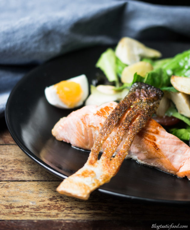 a photo of crispy salmon skin served over a cooked salmon portion, beside a nicoise salad.