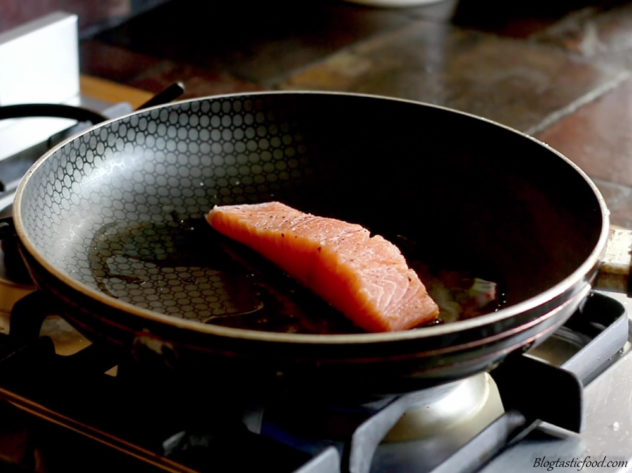a photo of salmon frying in a pan skin side down.