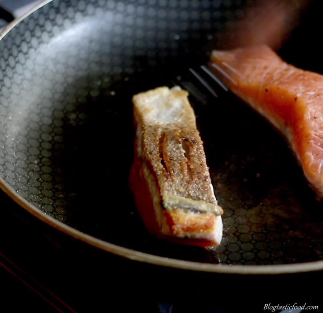 a photo of salmon searing in a pan skin side up.