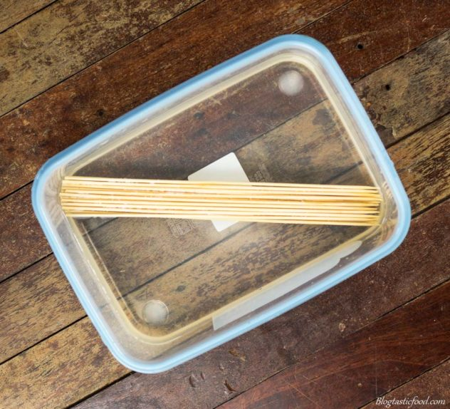 a hanful of wooden skewers in a container of water.