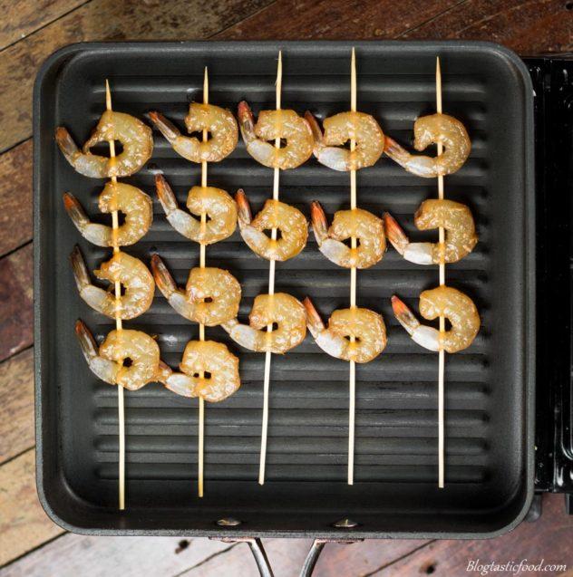 teriyaki prawn skewers being grilled in a griddle pan.