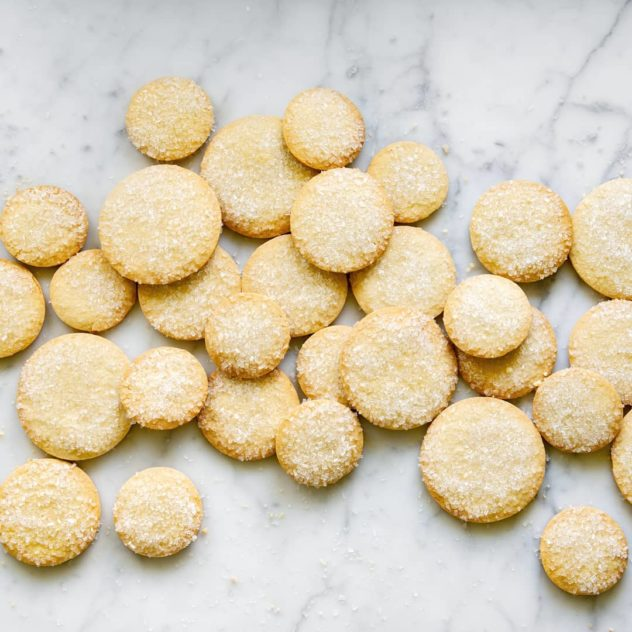 An overhead photo of french butter cookies piled up against one another.