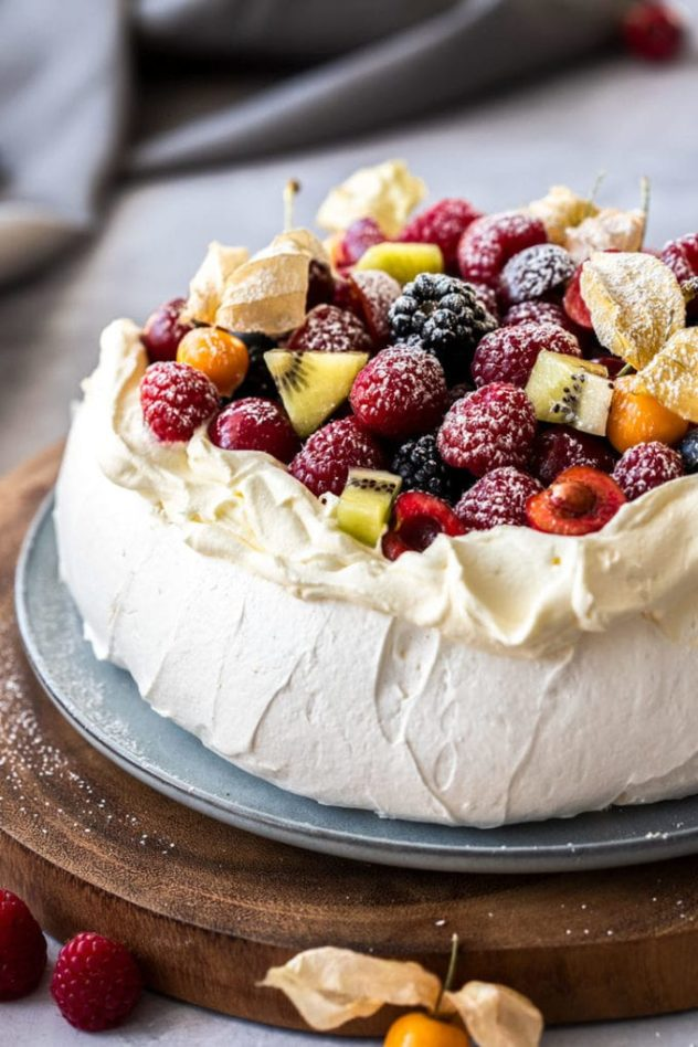 A large pavlova served on a blue plate, garnished with berries and kiwi fruit.
