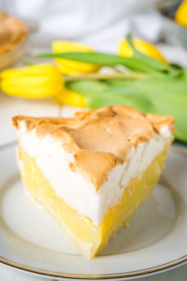 A front view of a slice of lemon meringue pie.