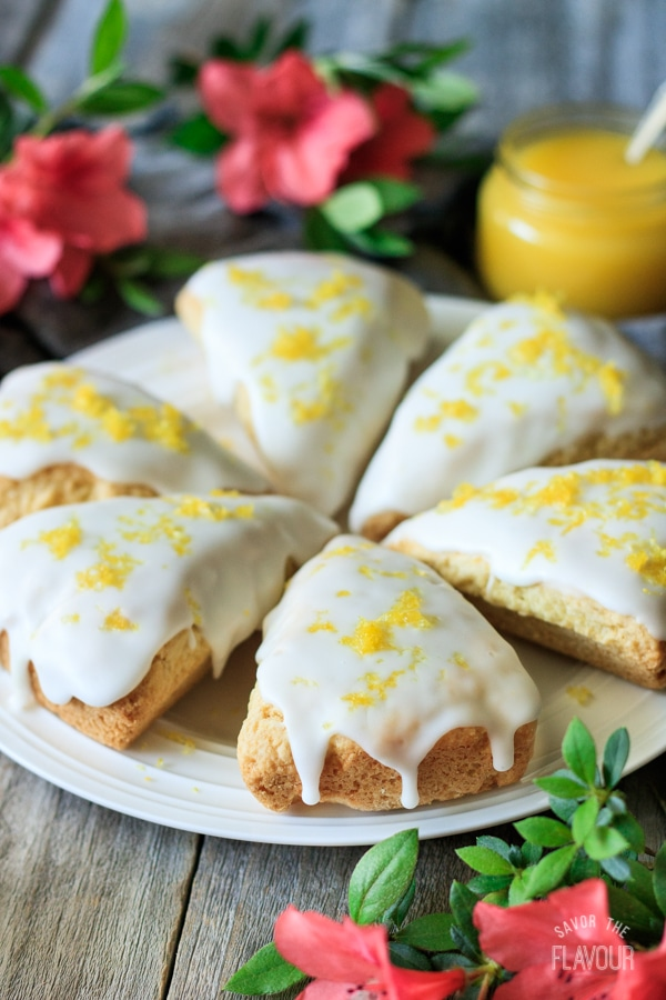 6 lemon scones served in a circle on a white plate, garnished with lemon zest.
