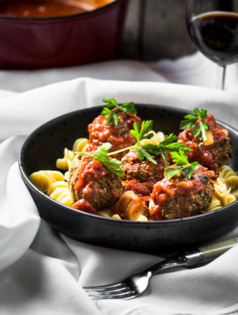 Homemade tomato sauce over lentil meatballs on pasta in a bowl over a white tablecloth.