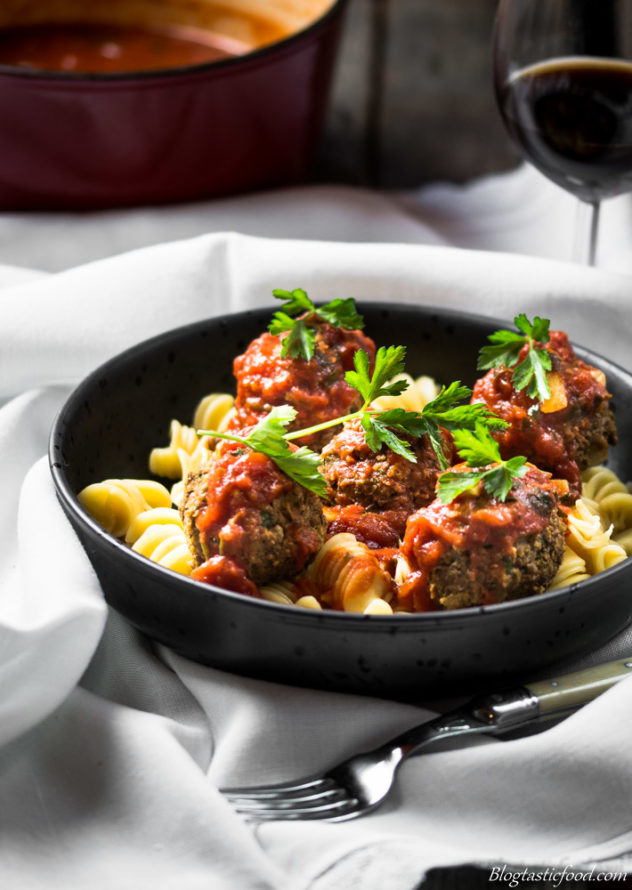 Tomato sauce, lentil meatballs and pasta in a bowl with a glass of red wine in the background.