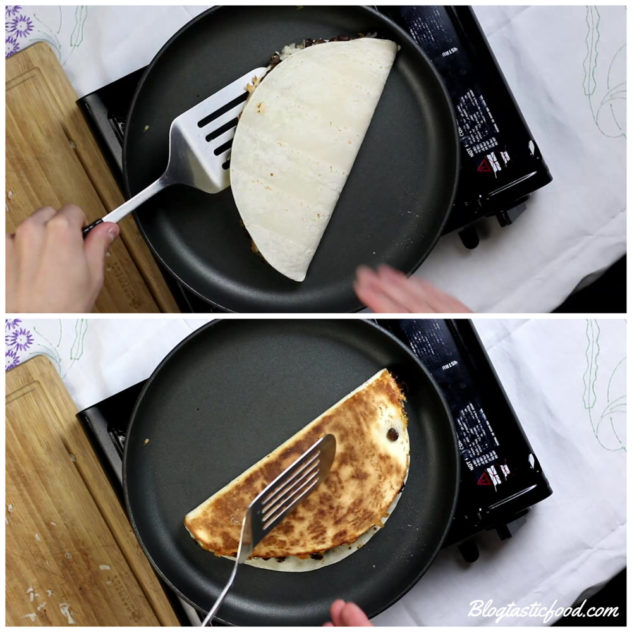 a black bean quesadilla that is toasting in a pan getting flipped.