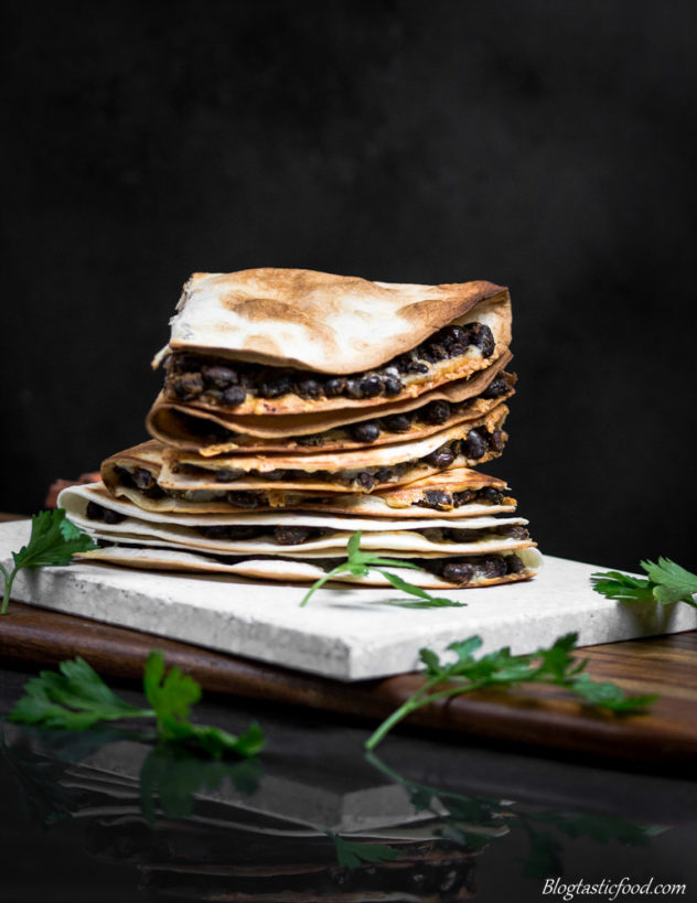 A stack of cheesy black bean quesadillas on a stone surface.