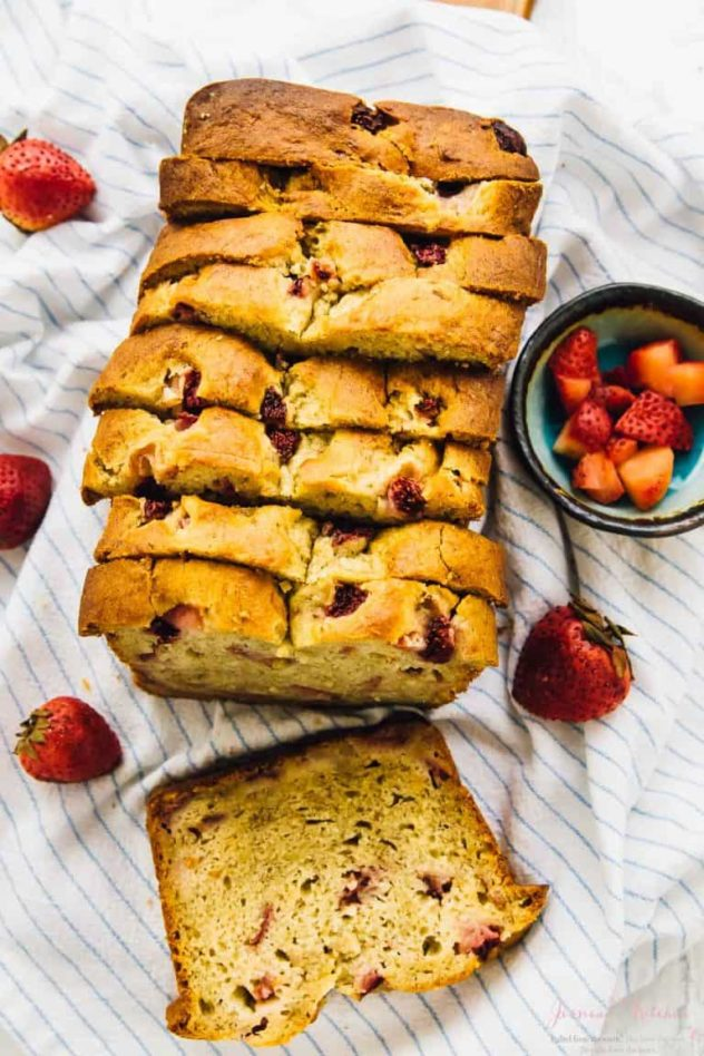 Strawberry banana bread sliced up on a white tea-towel, surrounded by fresh strawberries.