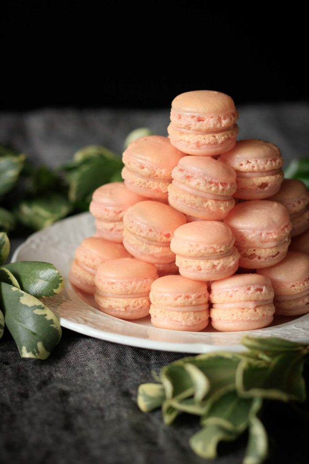 A large stack of strawberry macarons served on a white plate.