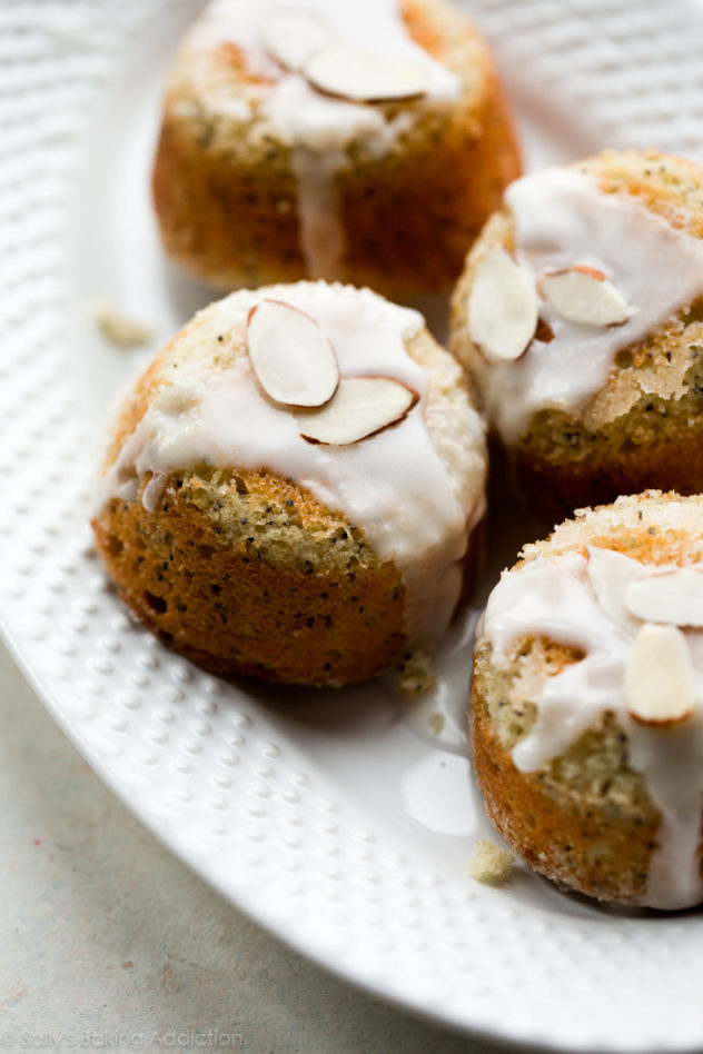 4 almond and poppyseed tea cakes served on a long white plate.