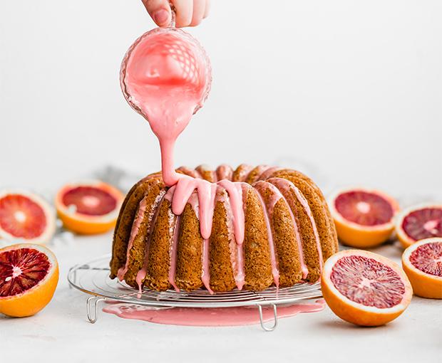 blood orange glaze being drizzled over blood orange cardamom bundt cake on a wire rack.