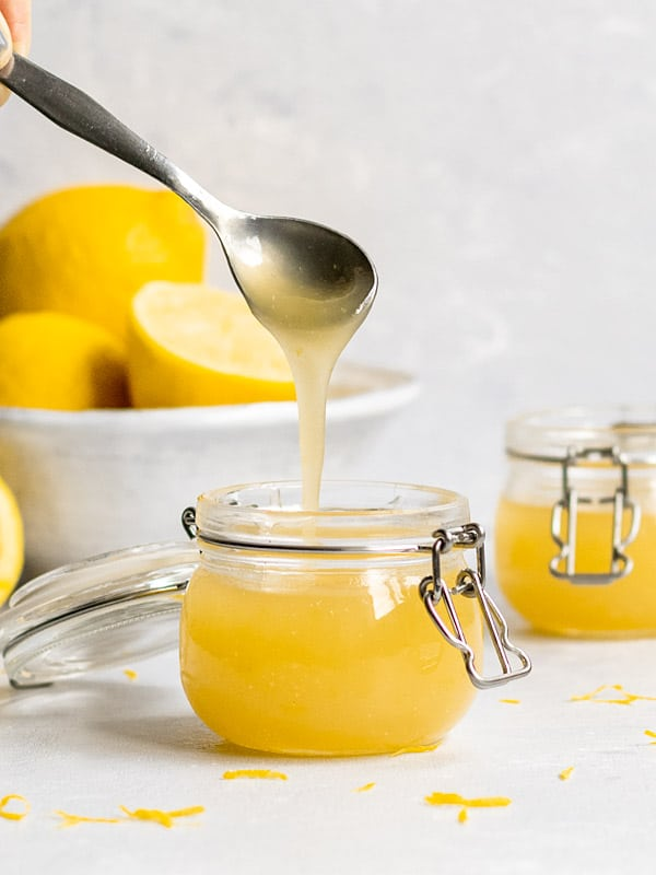 Vegan lemon curd drizzling off a spoon into a jar.
