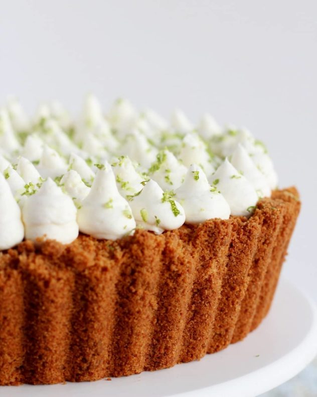 an eye level photo of a key lime cheesecake, garnished with lime zest.