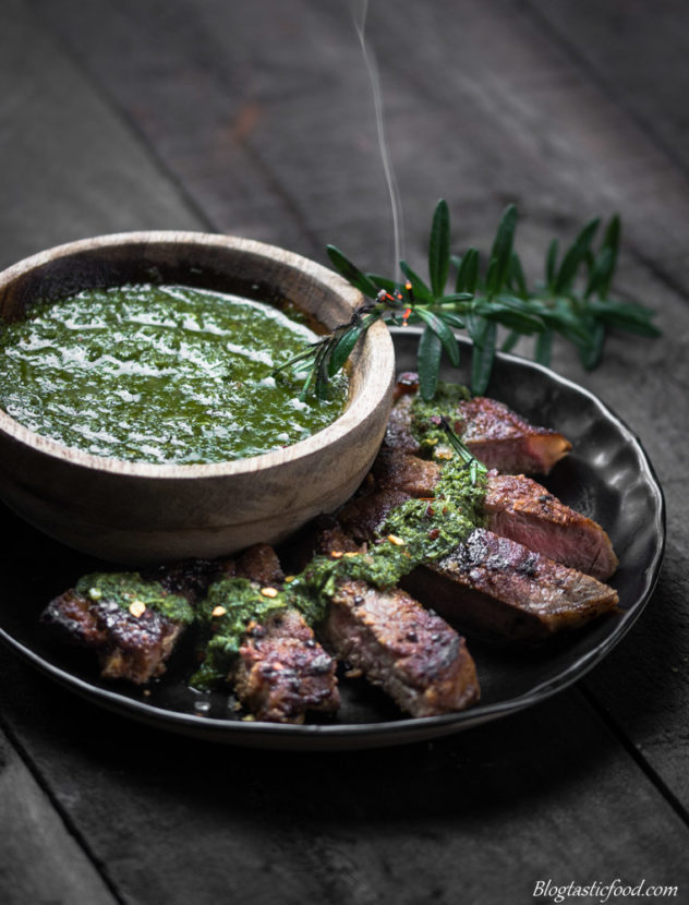 A black plate with sliced of sirloin steak and a bowl of chimichurri sauce on top.