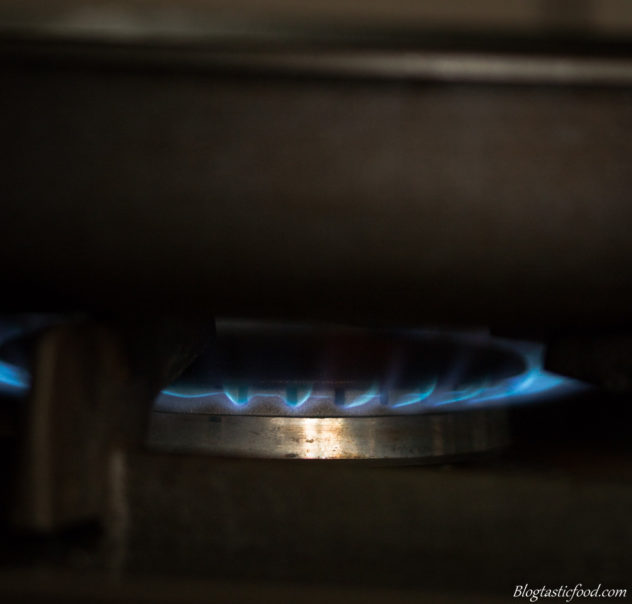 A close of a stove on high flame with a pan on top.