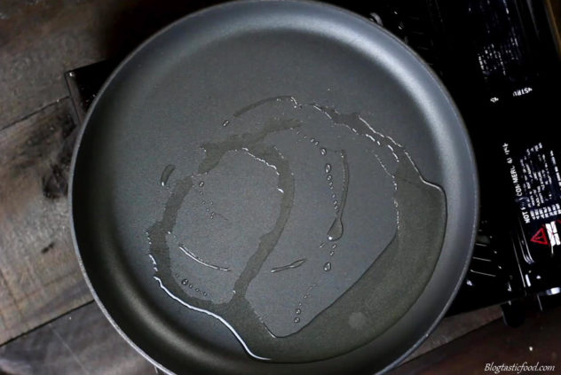 A photo of vegetable oil in a non stick frying pan.