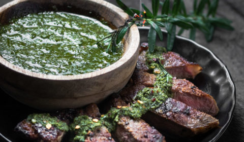 Slices of sirloin steak on a black plate beside a bowl of chimichurri sauce.