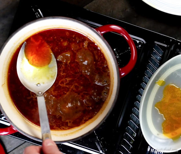 bbq sauce being skimmed with a large spoon.