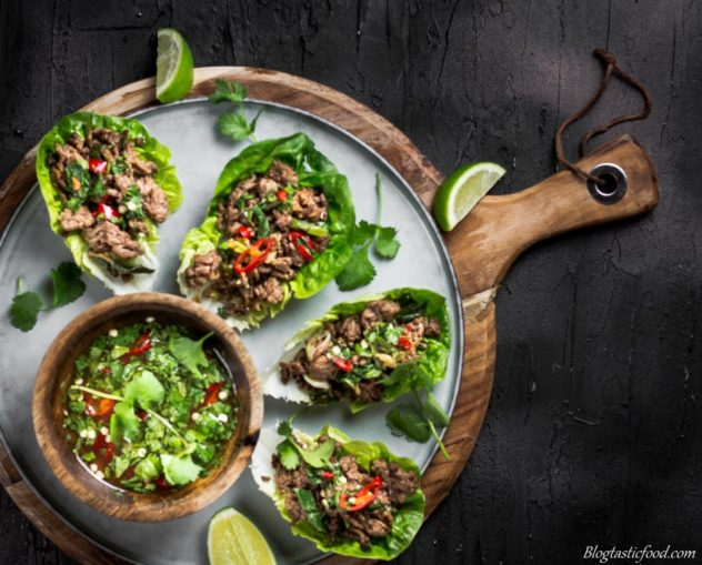 Beef lettuce wraps and thai dressing on a plate over a circular wooden board.