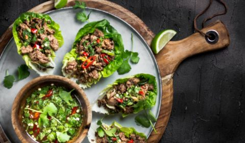 An overhead shot of beef lettuce wraps served on a greyish blue plate with Thai dressing.