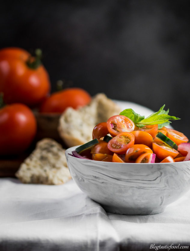 A cherry tomato salad in a small bowl with tomatoes and bread in the backgorund.
