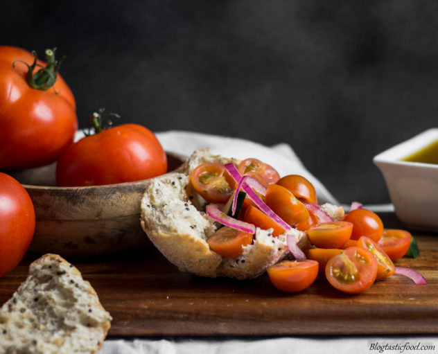 An eye level shot of cherry tomato salad on torn bread.