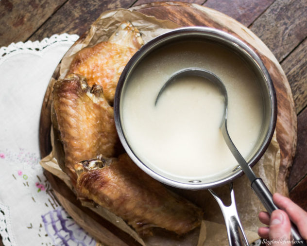 A pot of turkey gravy with a ladle in it, and roastey turkey wings beside it.
