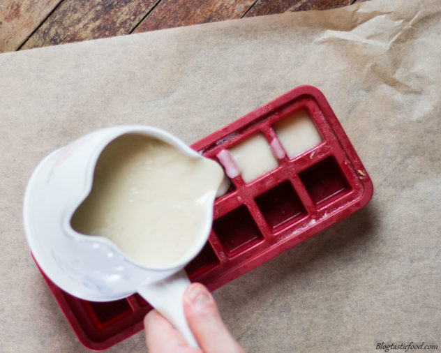 An ice cube tray being filled with turkey gravy.