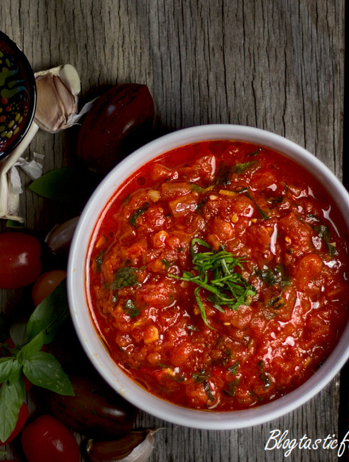 A white bowl filled with tomato sauce, beside cherry tomatoes, basil, garlic and a mini bowl of olive oil.