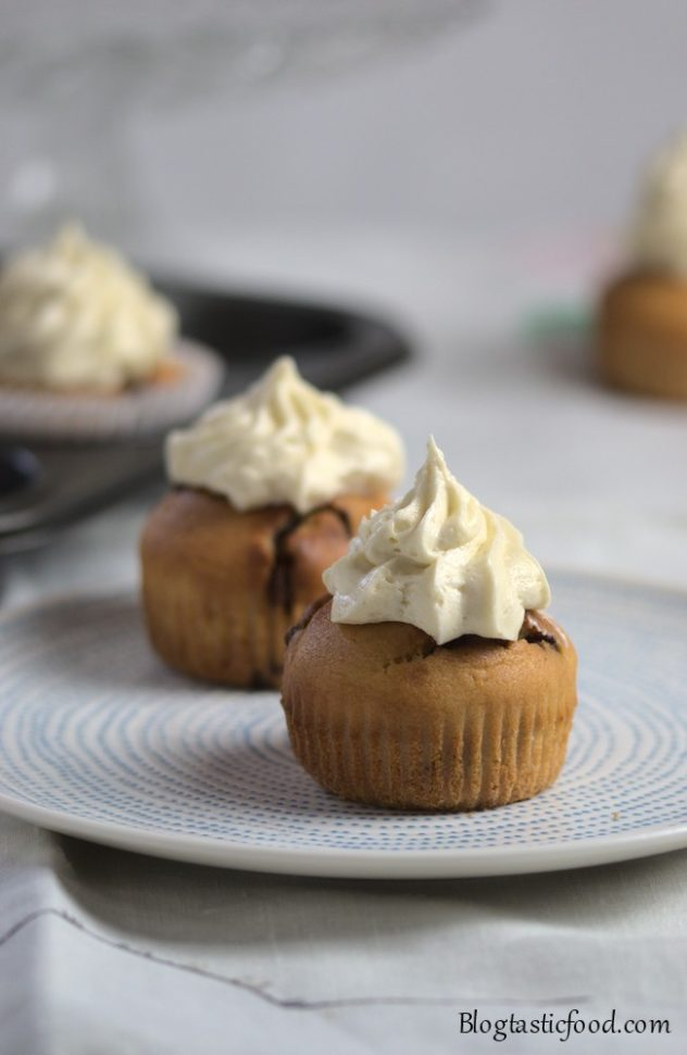2 banana and chocolate chip muffins served on a white plate.