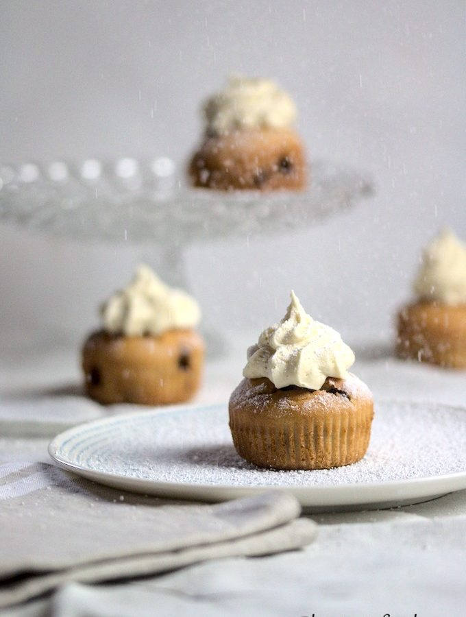 4 banana and chocolate chip muffins in a white tablecloth with icing sugar being dusted on top.