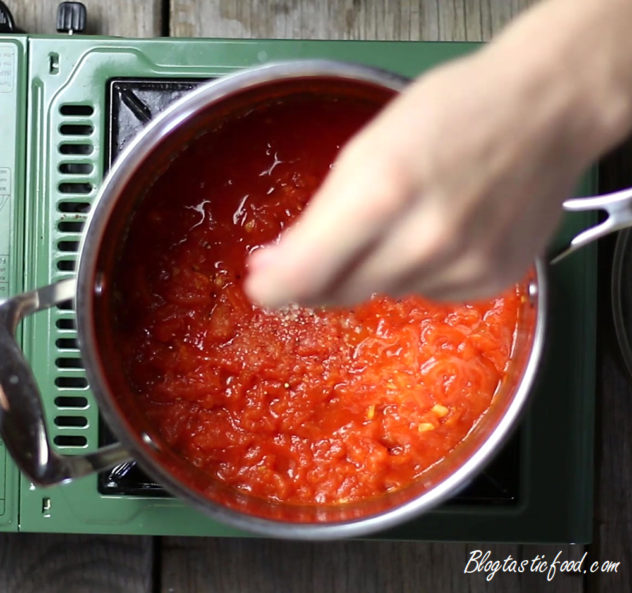 Someone adding a pinch of sugar to a pot of tomato sauce.