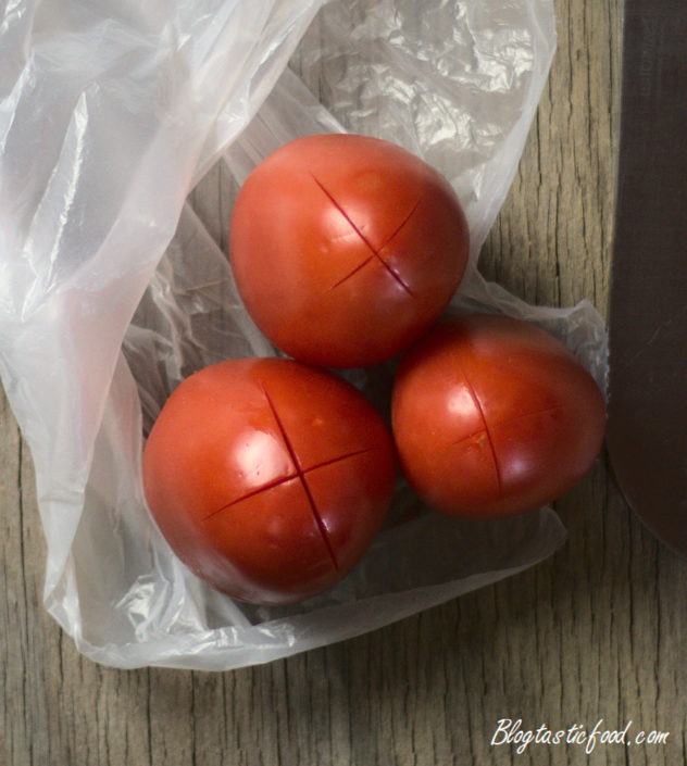 A close up of roma tomatoes with incisions in them.