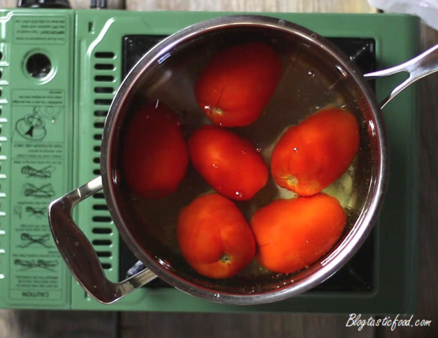 Roma tomatoes boiling in a pot of water.