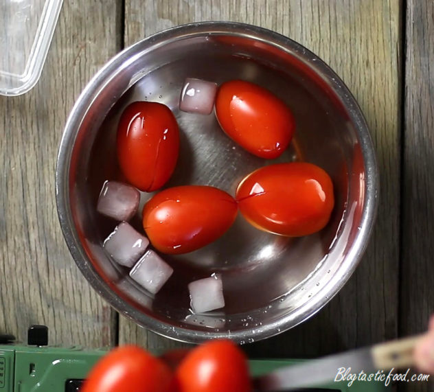 Par-boiled tomatoes in a bowl of cold water.