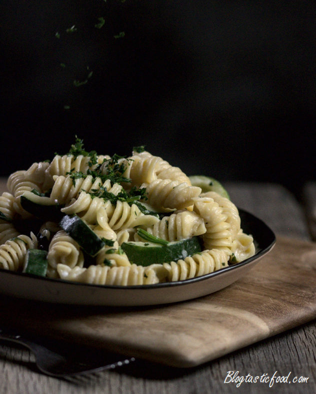 Creamy Spinach and Courgette Pasta on a black plate, with parlsey being sprinkled on top.
