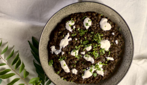 Lentil curry served in a bowl, garnished with sour cream and coriander.