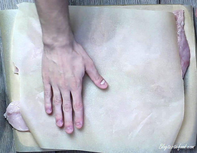 A sheet of baking paper over chicken breasts.