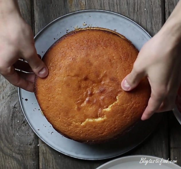 The final cake layer beng placed on top to make a Victoria sponge cake.