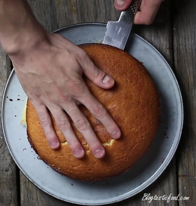 A cake being sliced in half with a bread knife.f